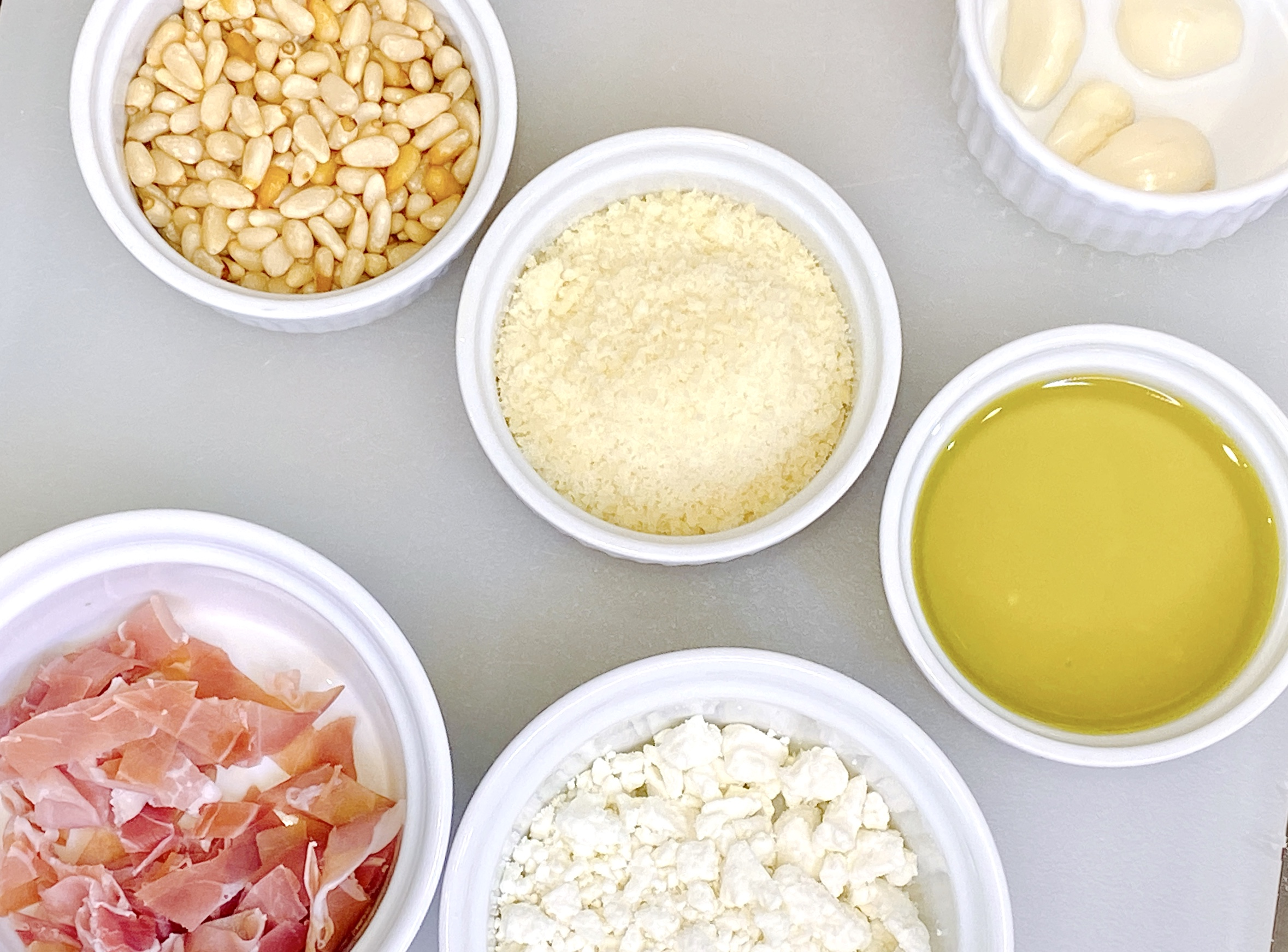 ingredients to make pesto flatbread with prosciutto, pinenuts, goat cheese and more.