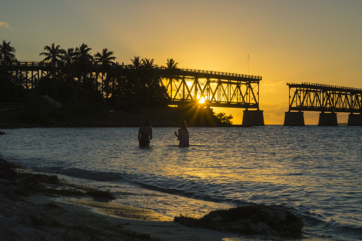 This sunset view of two girls in the water at Bahia Honda State Park in the Florida Keys. The Keys do not have a lot of sand beaches and this is arguably the most picturesque. The bridge silhouette in the background is the abandoned railway that used to run the length of the keys all the way to Key West. For sure a magical spot and scene.