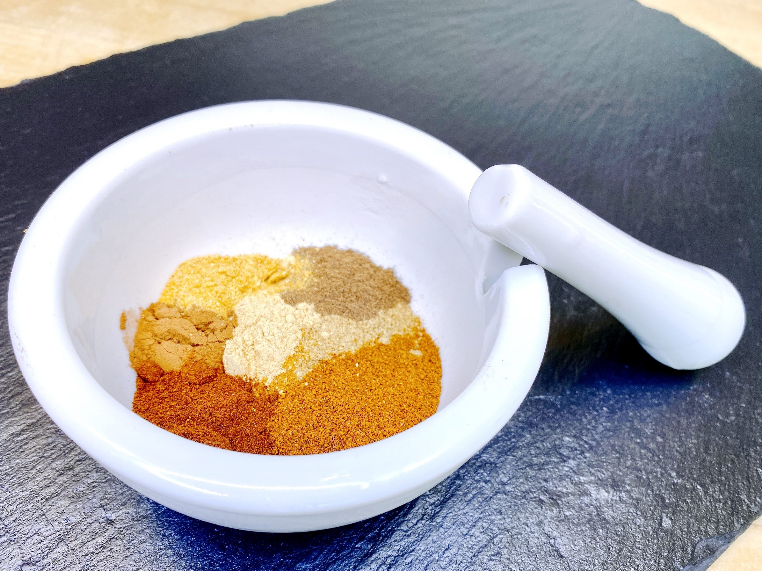 spices combined in a while mortar and pestle to make Moroccan Chermoula spice mix