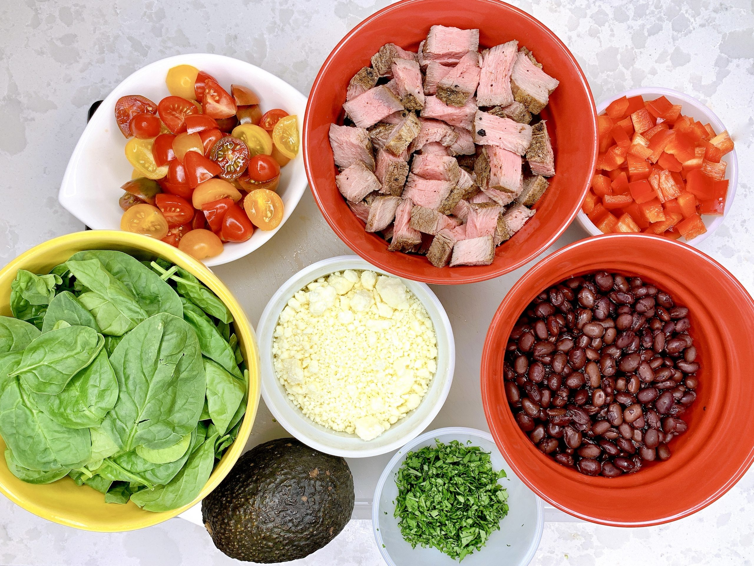 overhead view of chopped ingredients in bowls as part of recipe for Chipotle Steak Bowl with Black Beans and Quinoa
