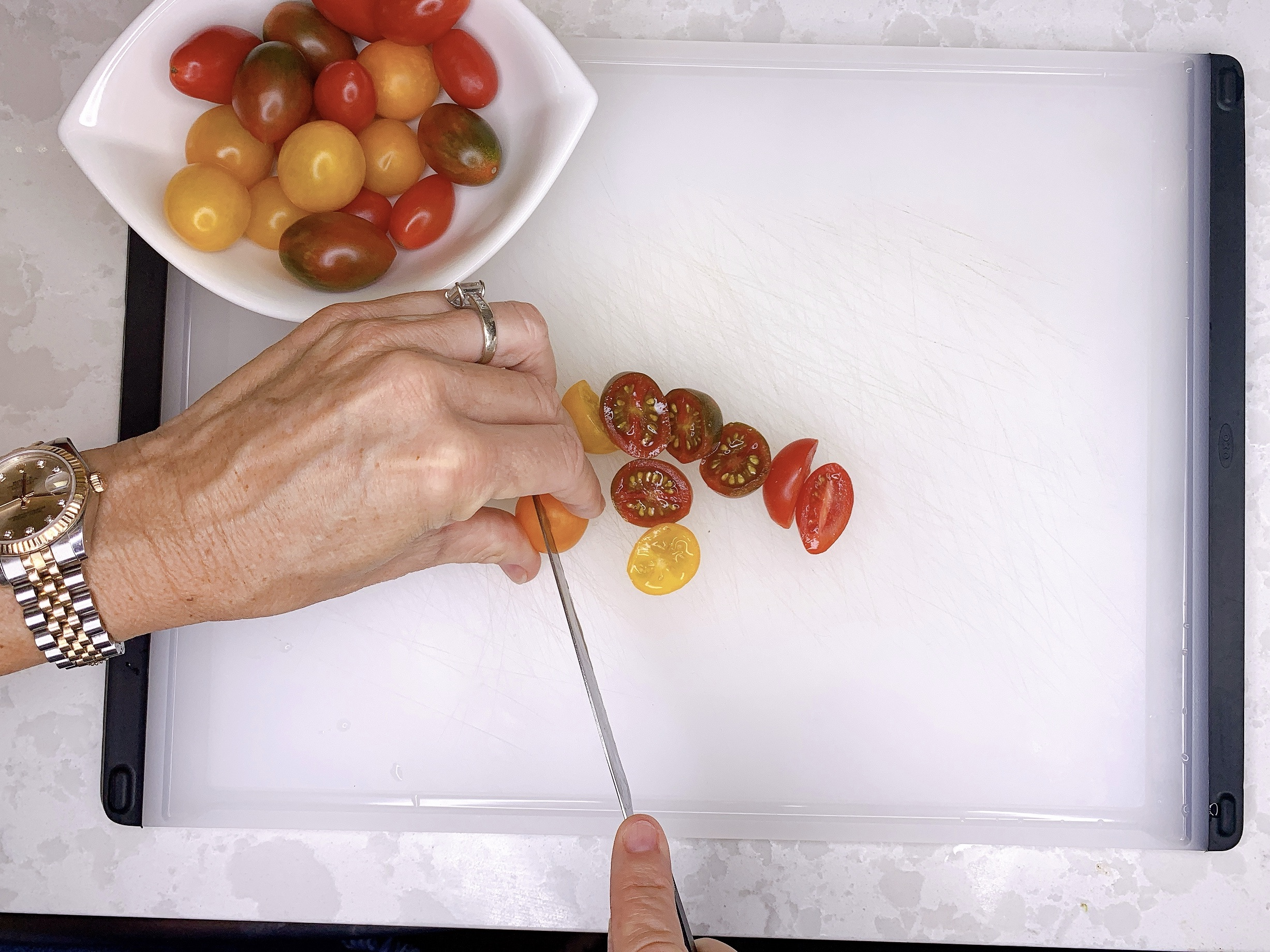 Woman's hands from above as she slices baby heirloom tomatoes in halves