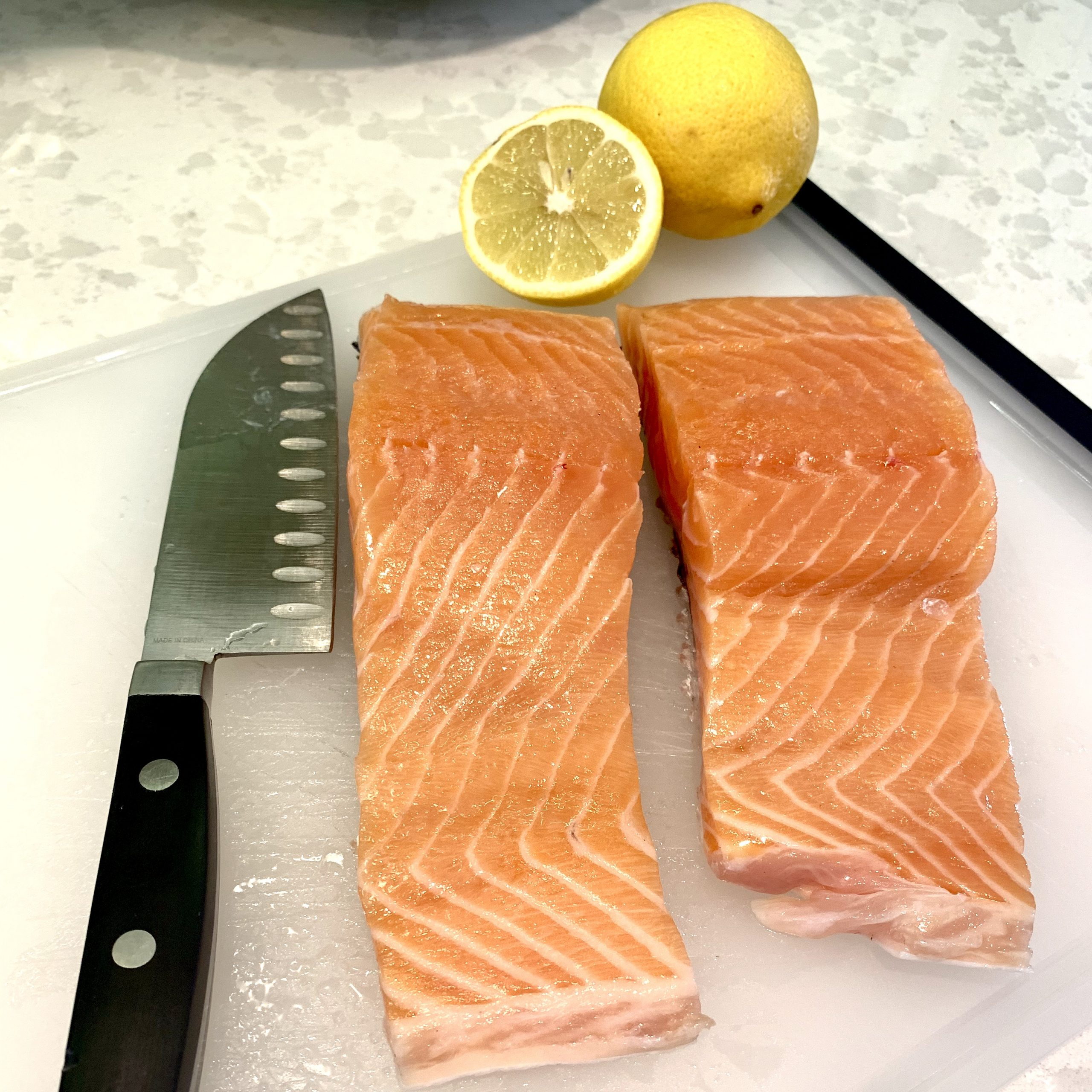 two pieces of raw salmon ready to be cooked