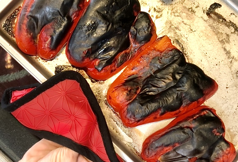 charred red peppers being removed from oven after roasting