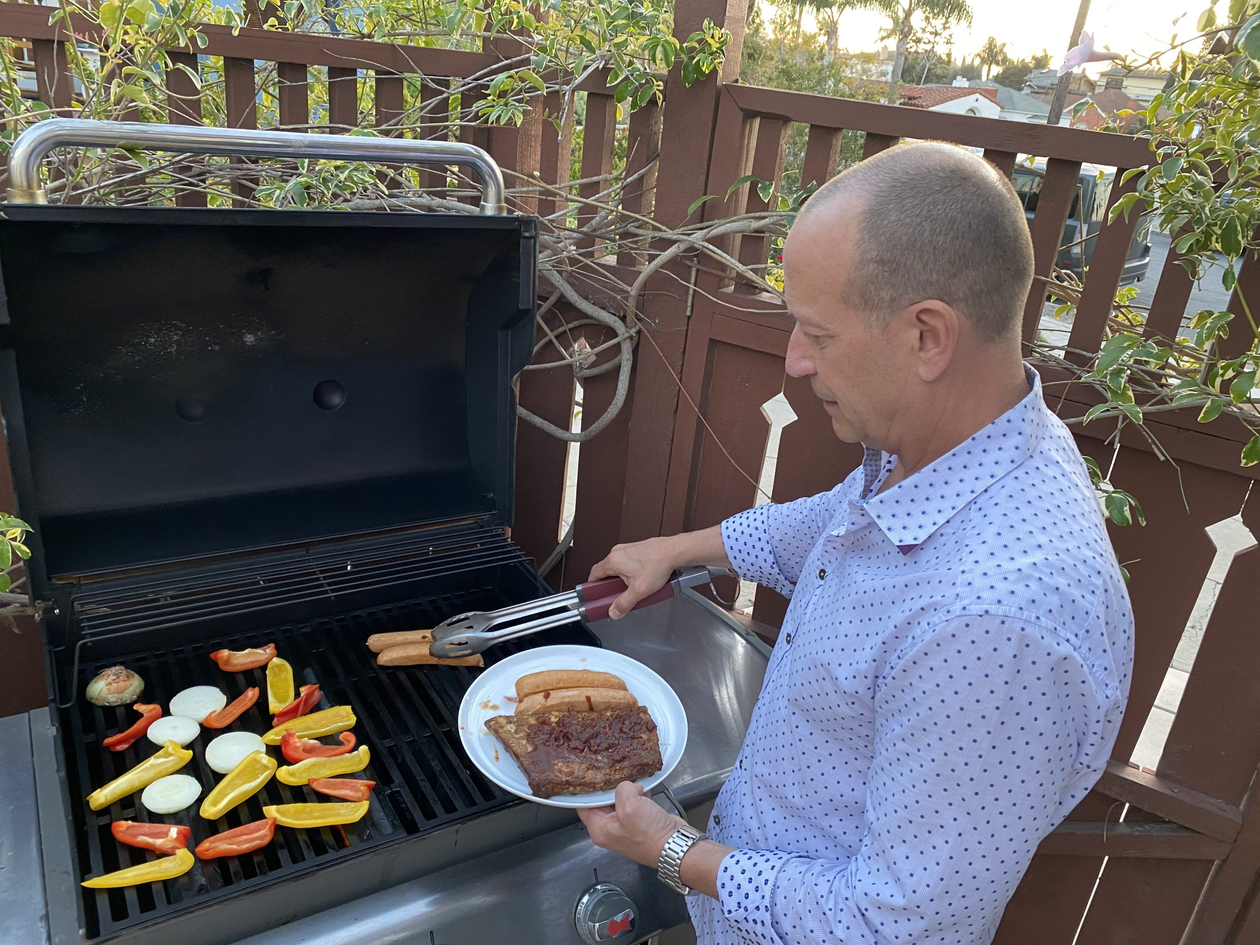 man grills ribs, hot dogs and vegetables on open barbeque