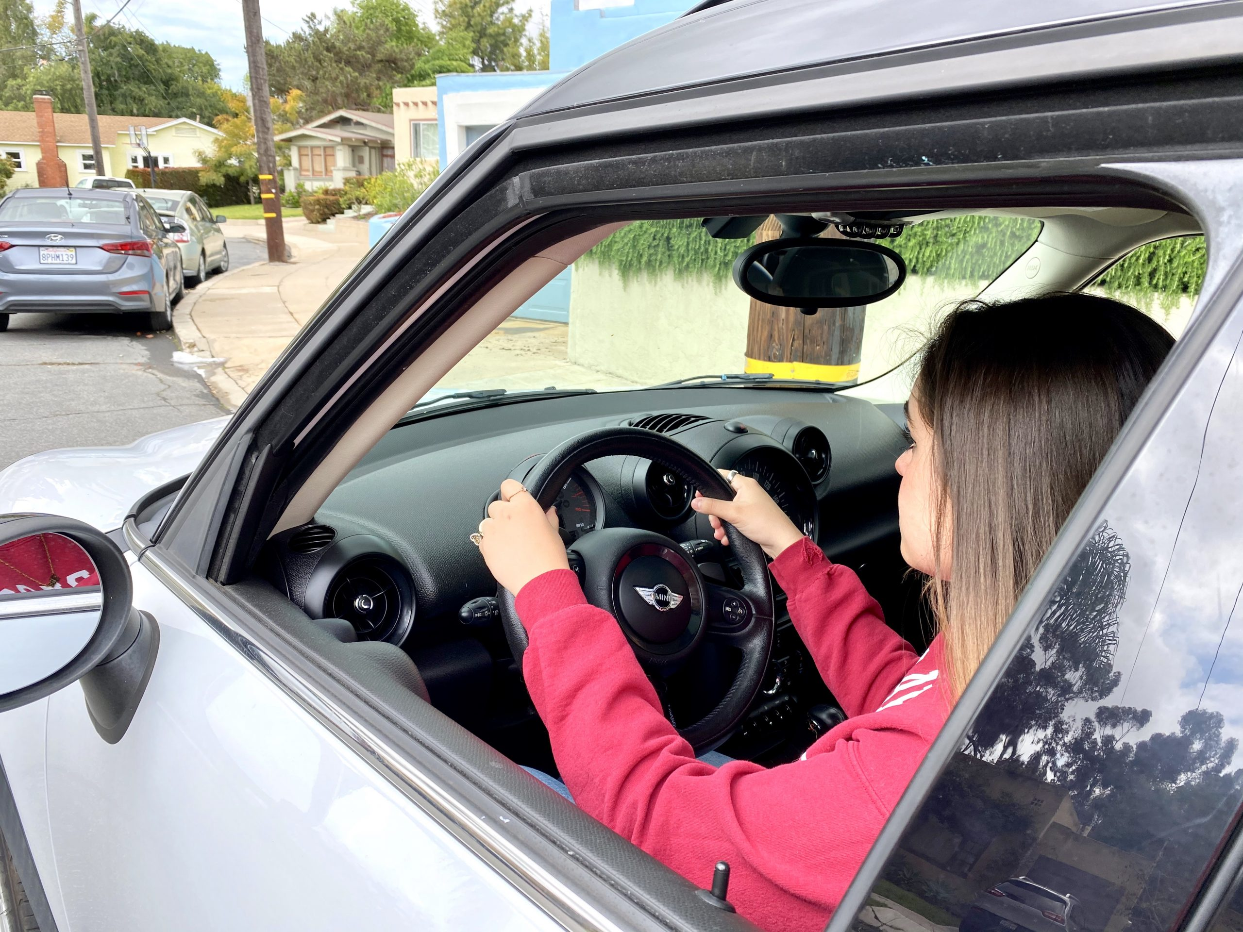 girl sits behind wheel of Mini Cooper Countryman