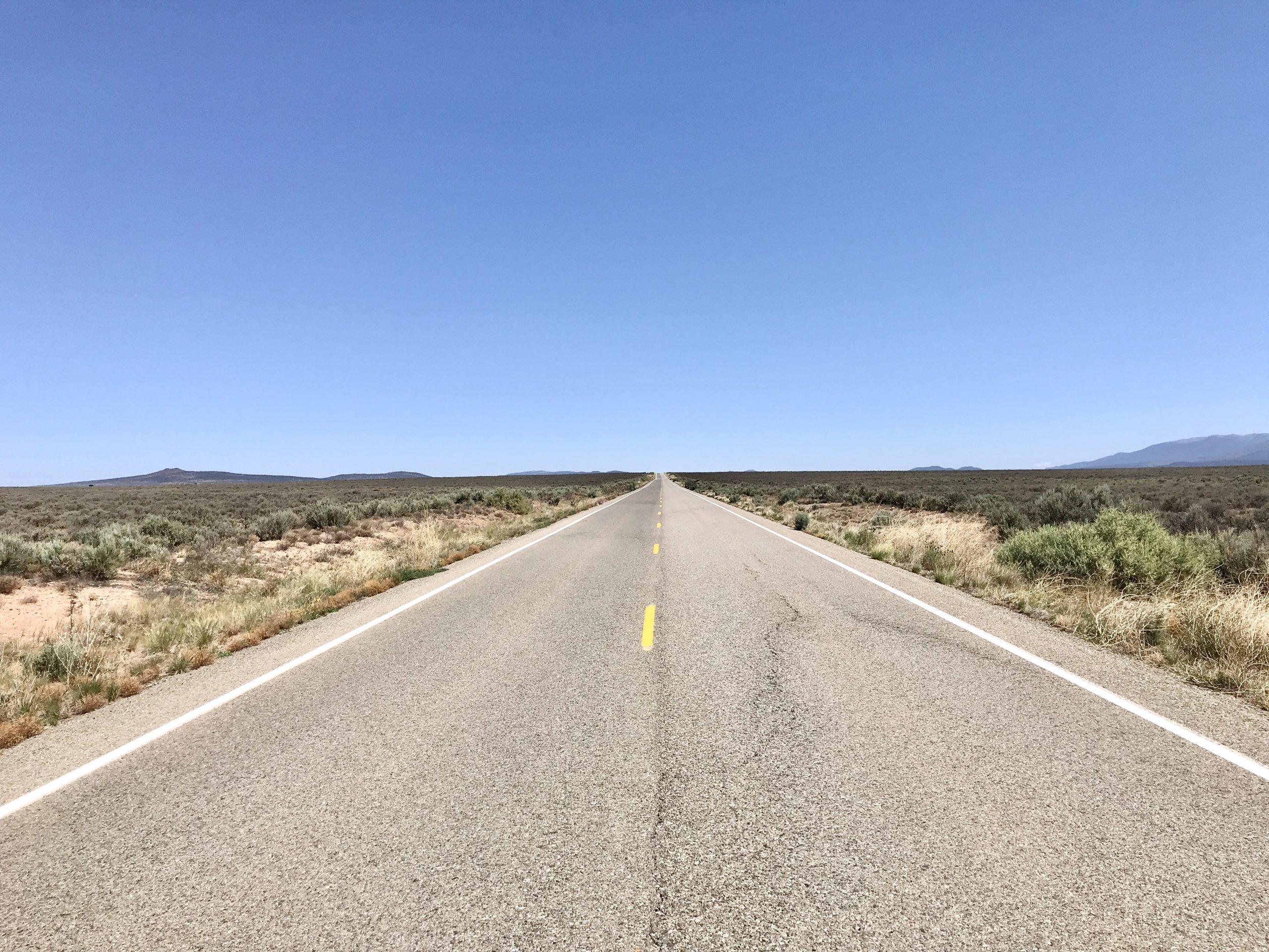 Empty road travels straight into the horizon near Taos, New Mexico
