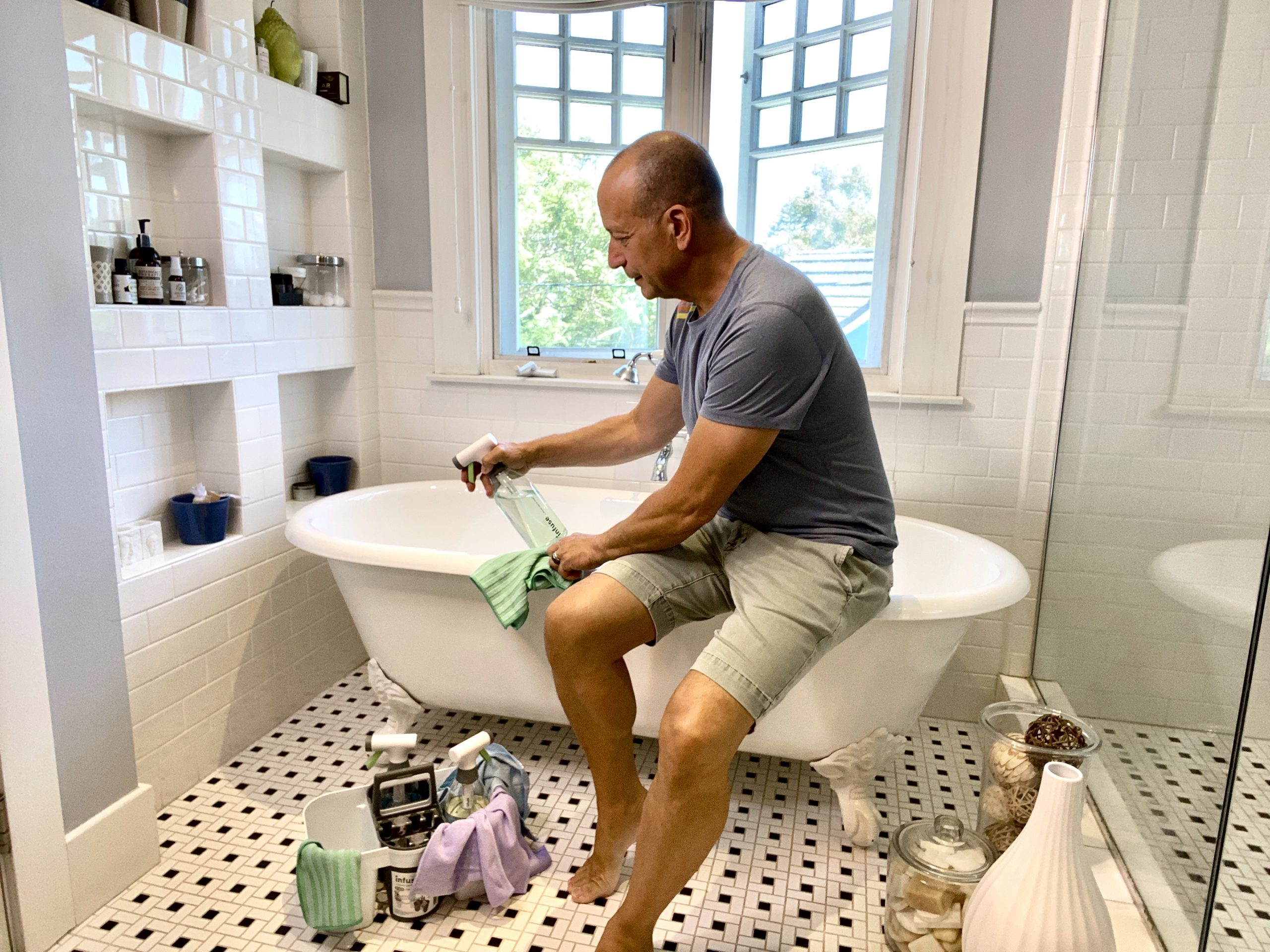 man cleaning bathroom tub with Infuse Cleaning Products
