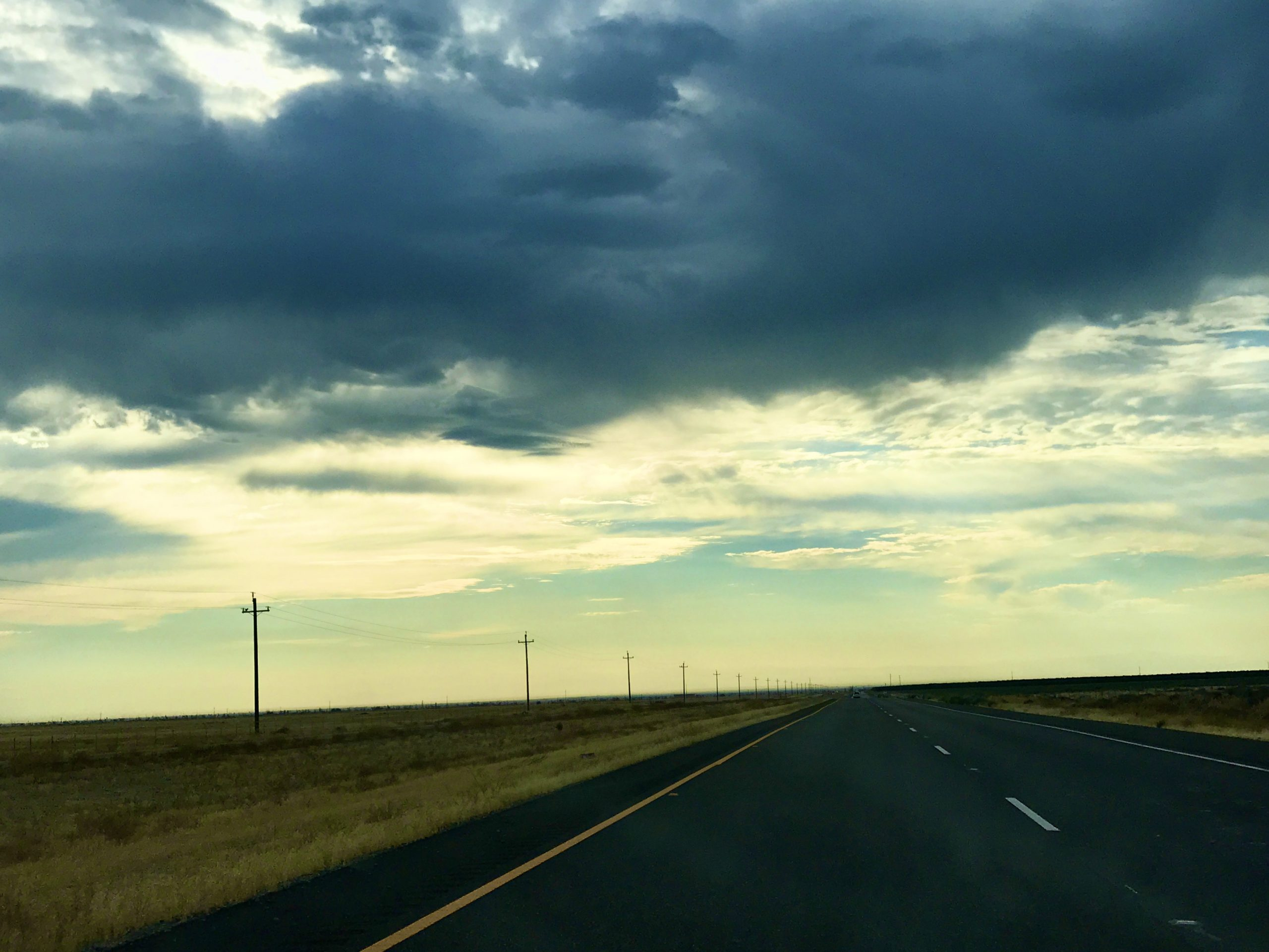 empty road with telephone poles and cloudy skies in Central California