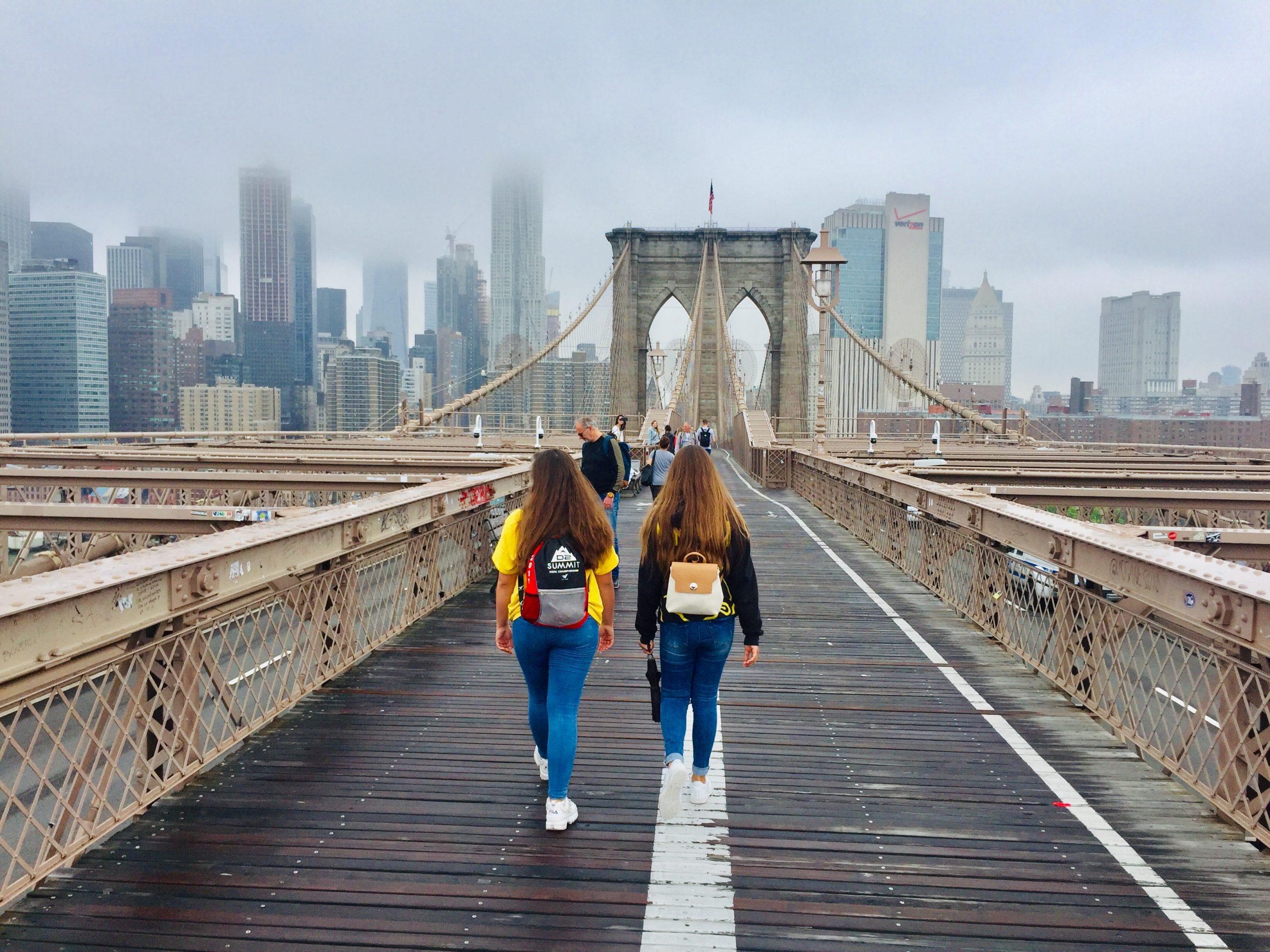 Two girls walk across the Brooklyn Bridge on an early foggy morning.