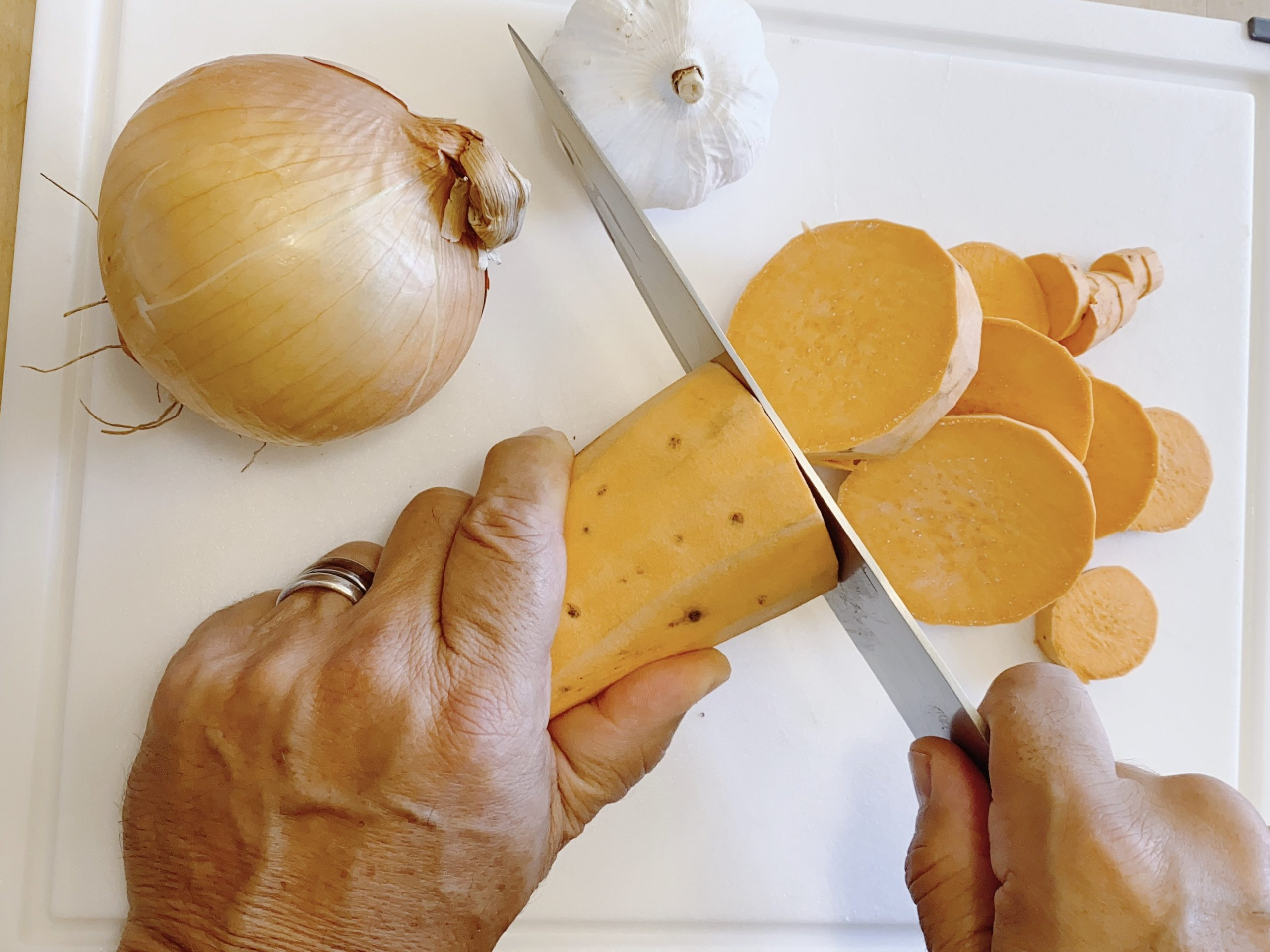 man slicing sweet potato on white cutting board with onion and garlic