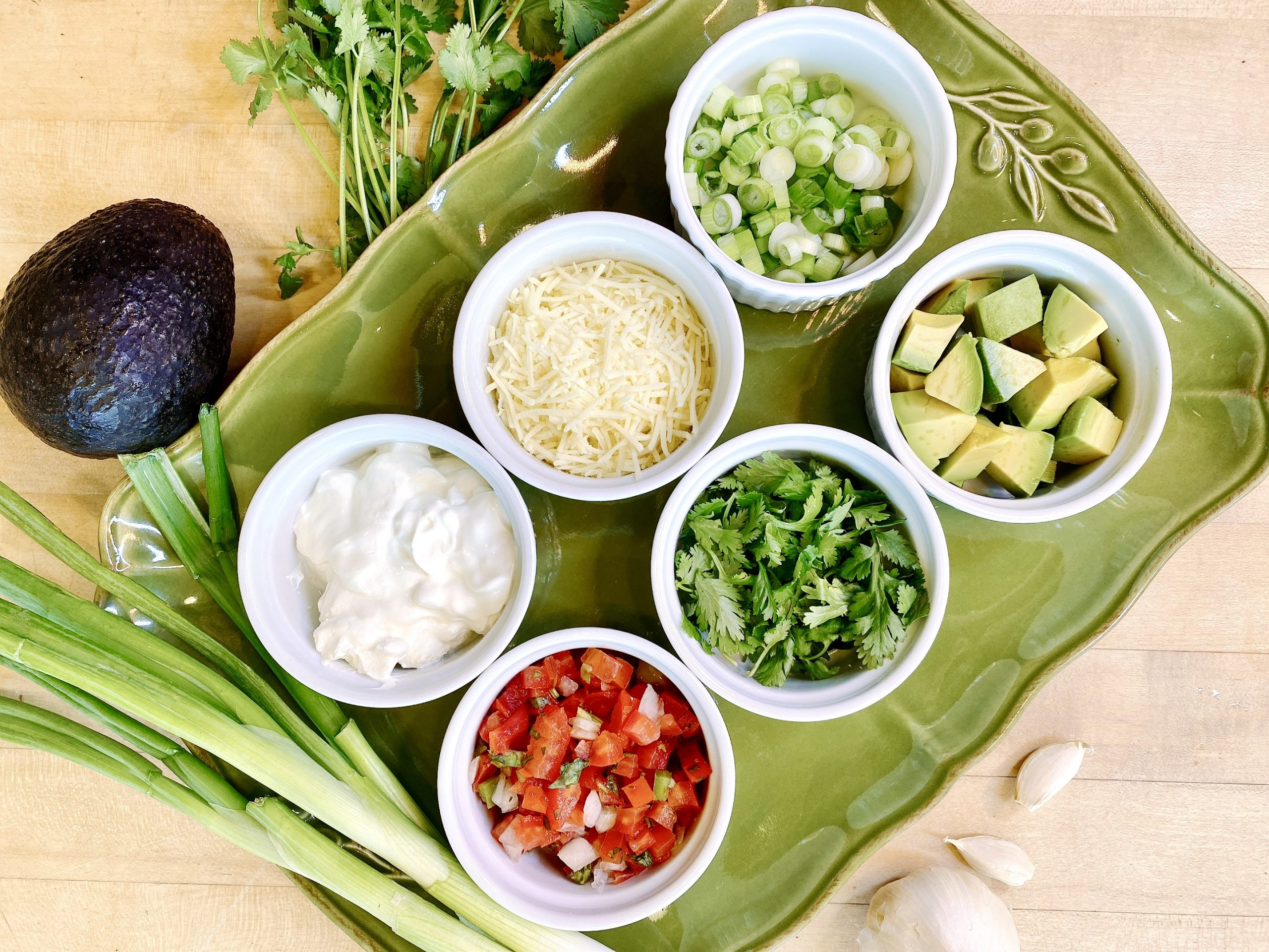 ramekins of chili toppings including sour cream, shredded cheese, green onions, chopped avocado, cilantro leaves and pico de gallo tomato salsa, arranged on a green platter
