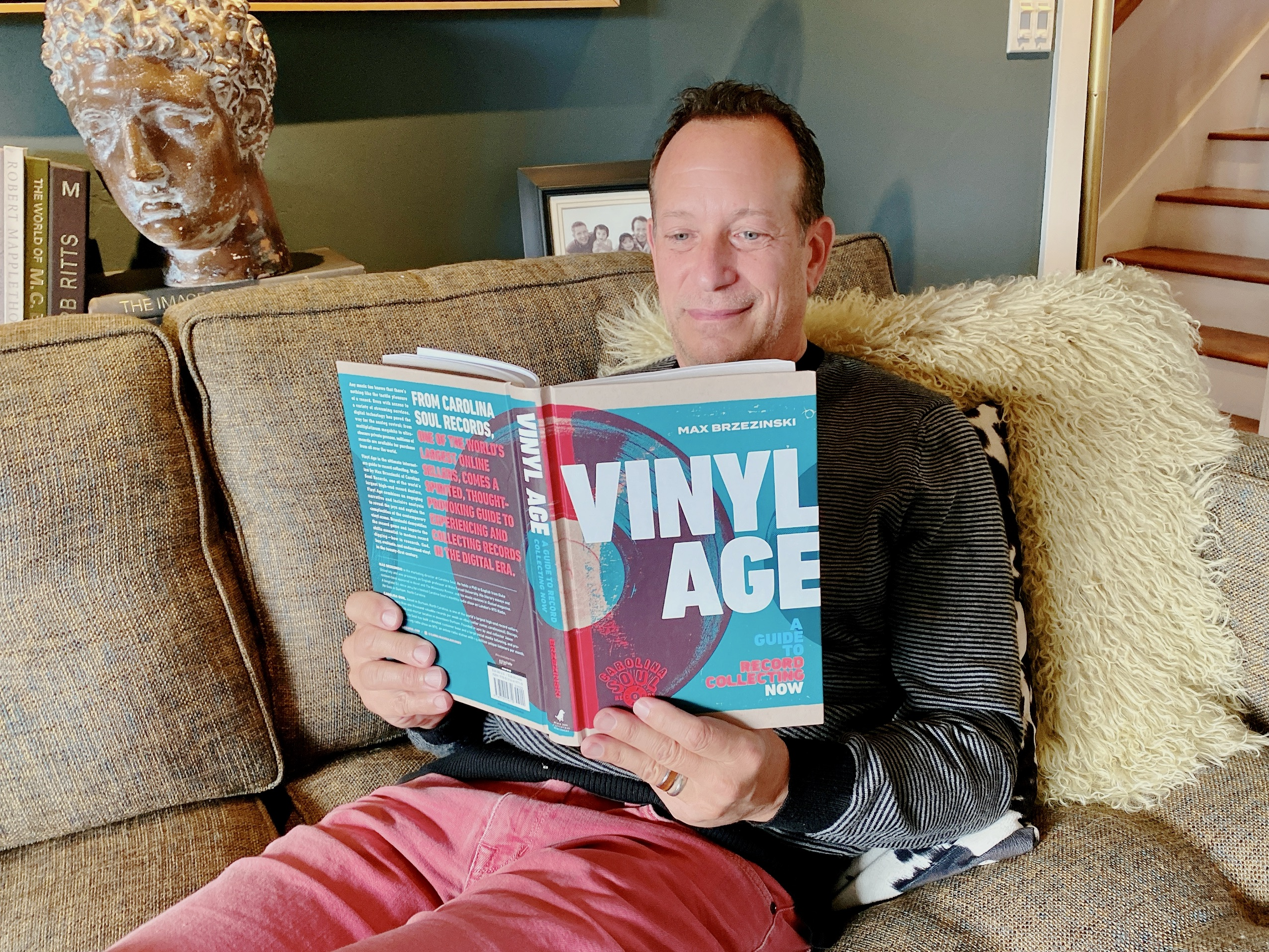 man on couch reading Vinyl Age: A Guide to Record Collecting Now by Max Brzezinski and Carolina Soul