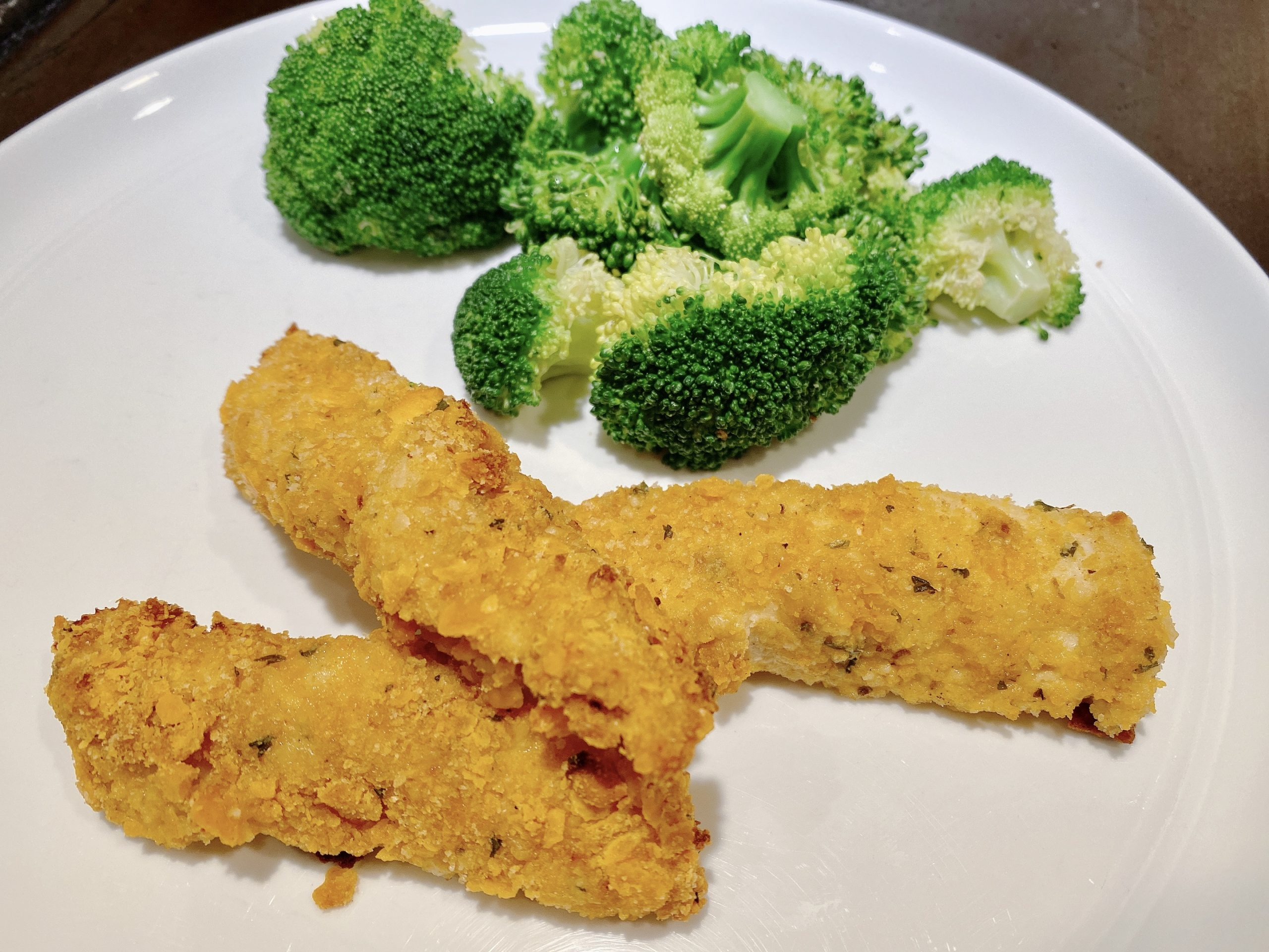 Homemade Crispy Chicken Tenders on dinner plate with steamed broccoli crowns