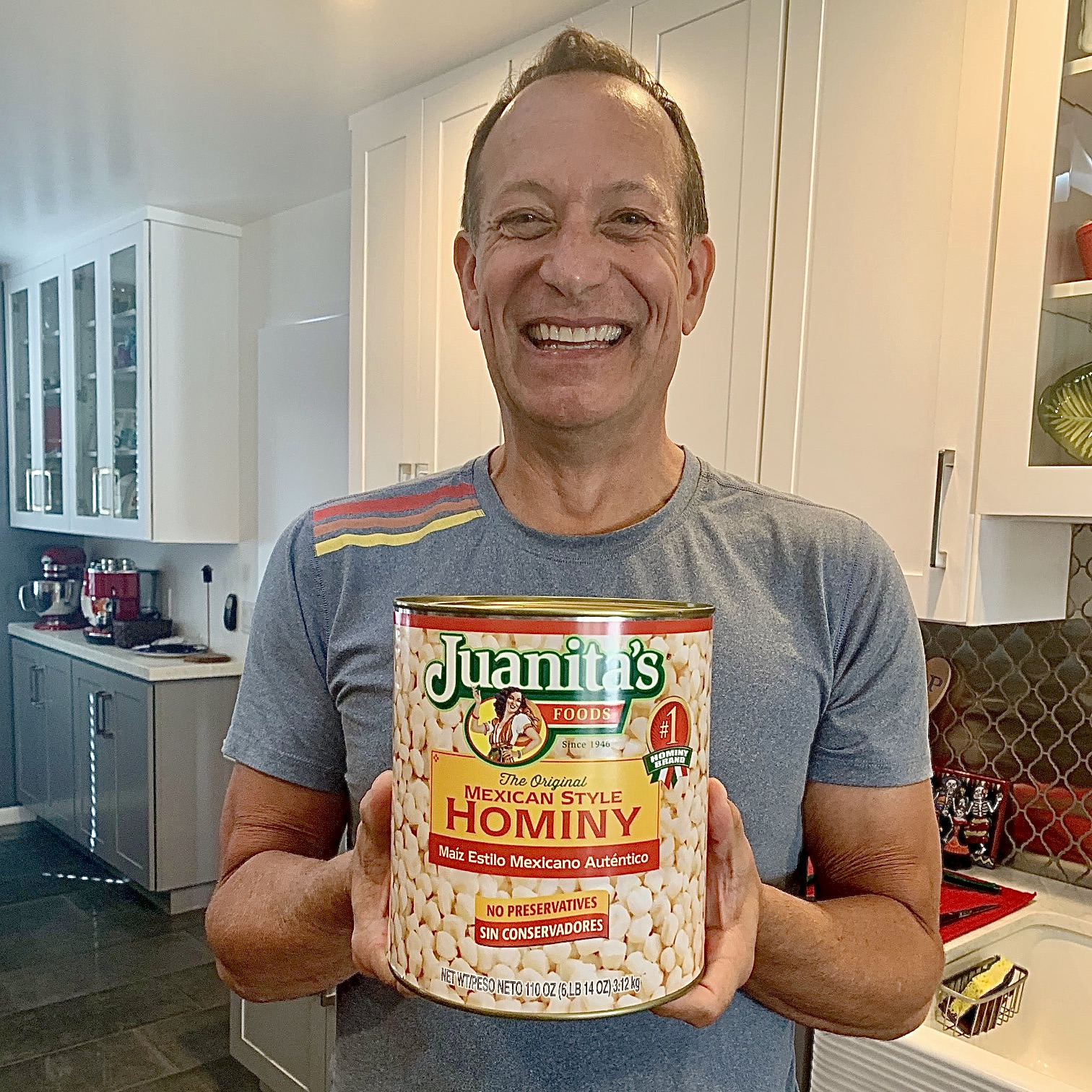 man holding giant can of Juanita's brand Mexican-style Hominy