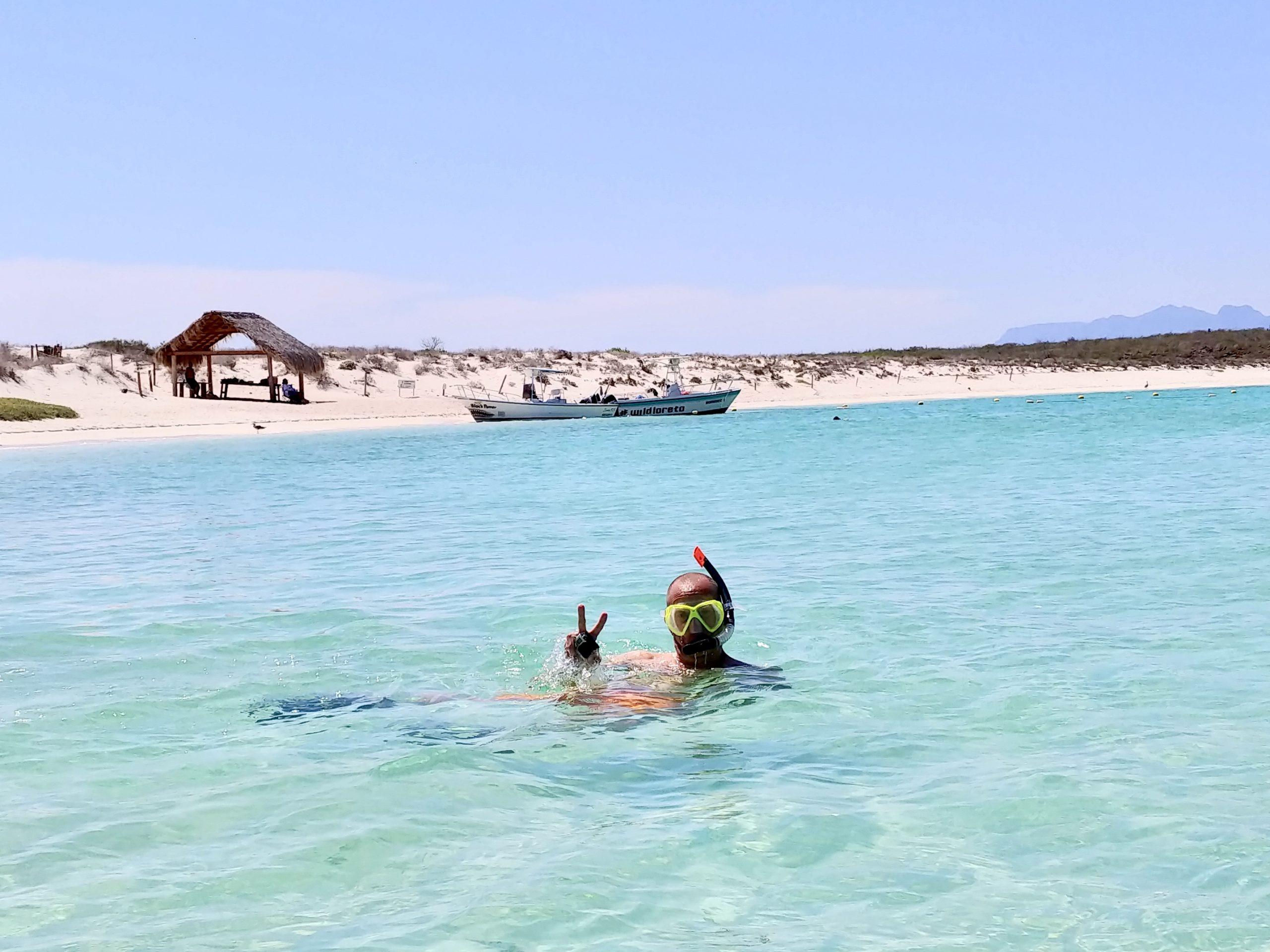 man snorkels off the beaches of Isla Coronado in Loreto, Mexico