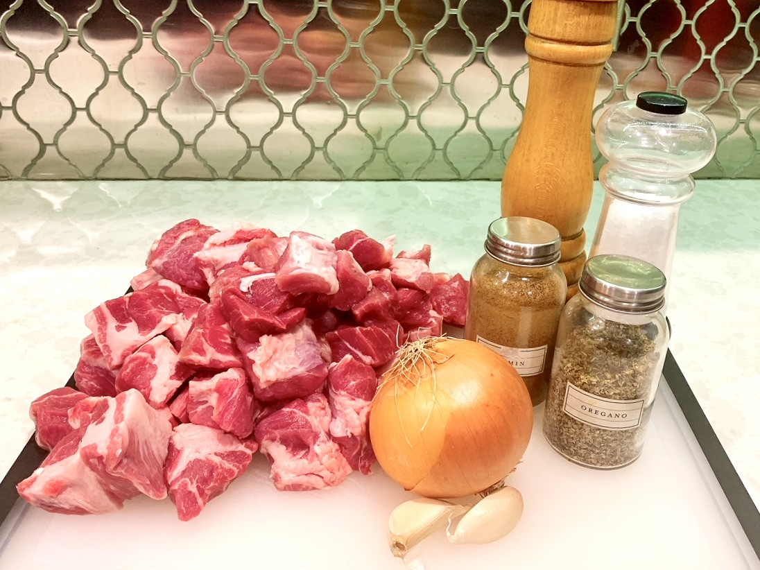 ingredients to make carnitas, including cubed pork roast, onion, garlic, oregano, and more.