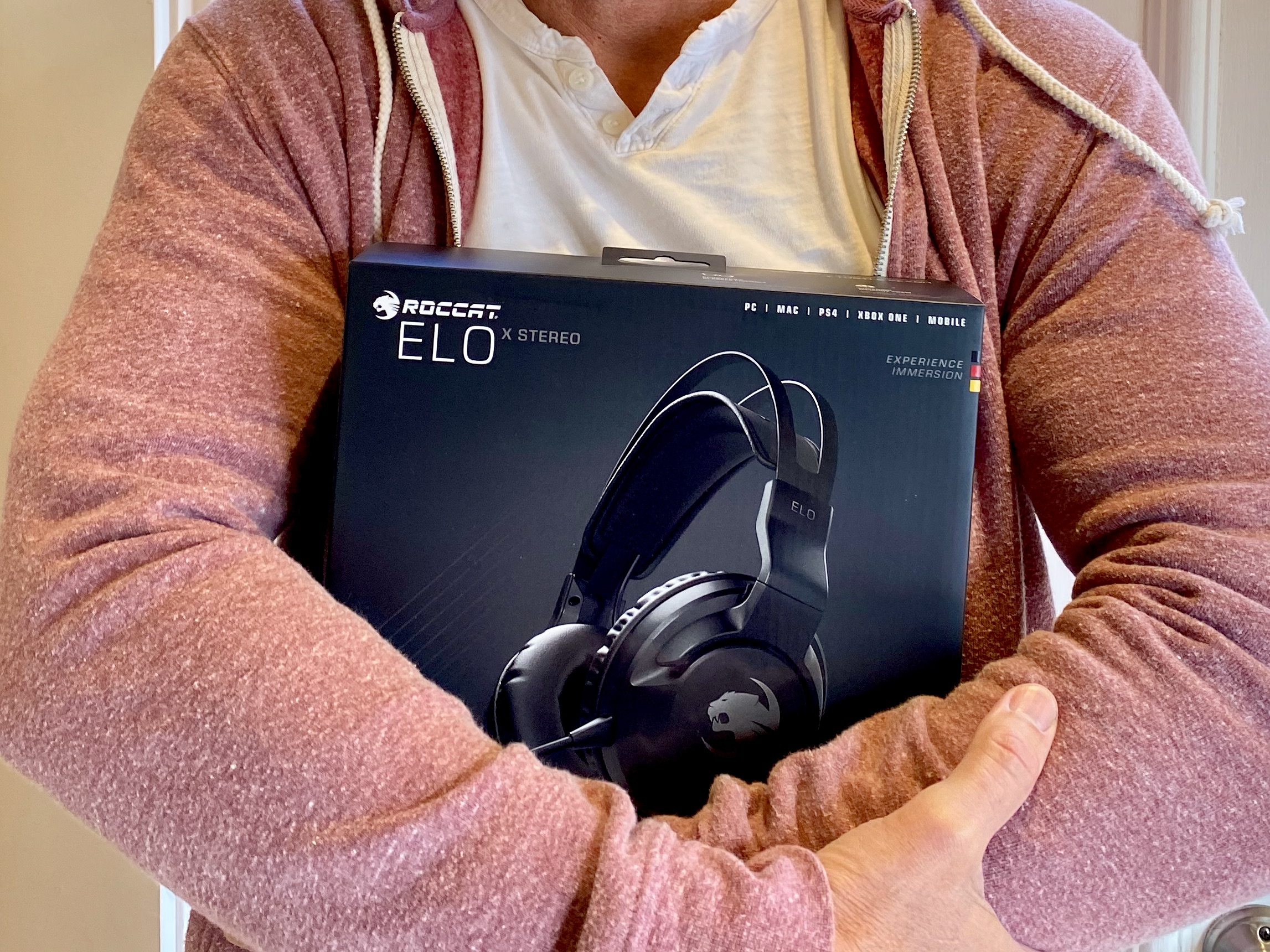 Man holding The ROCCAT Elo X Stereo Gaming Headset in his arms