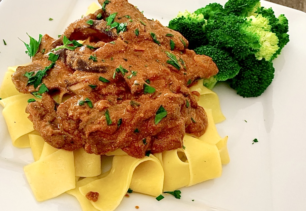 Beef Stroganoff served over egg noodles with a side of broccoli