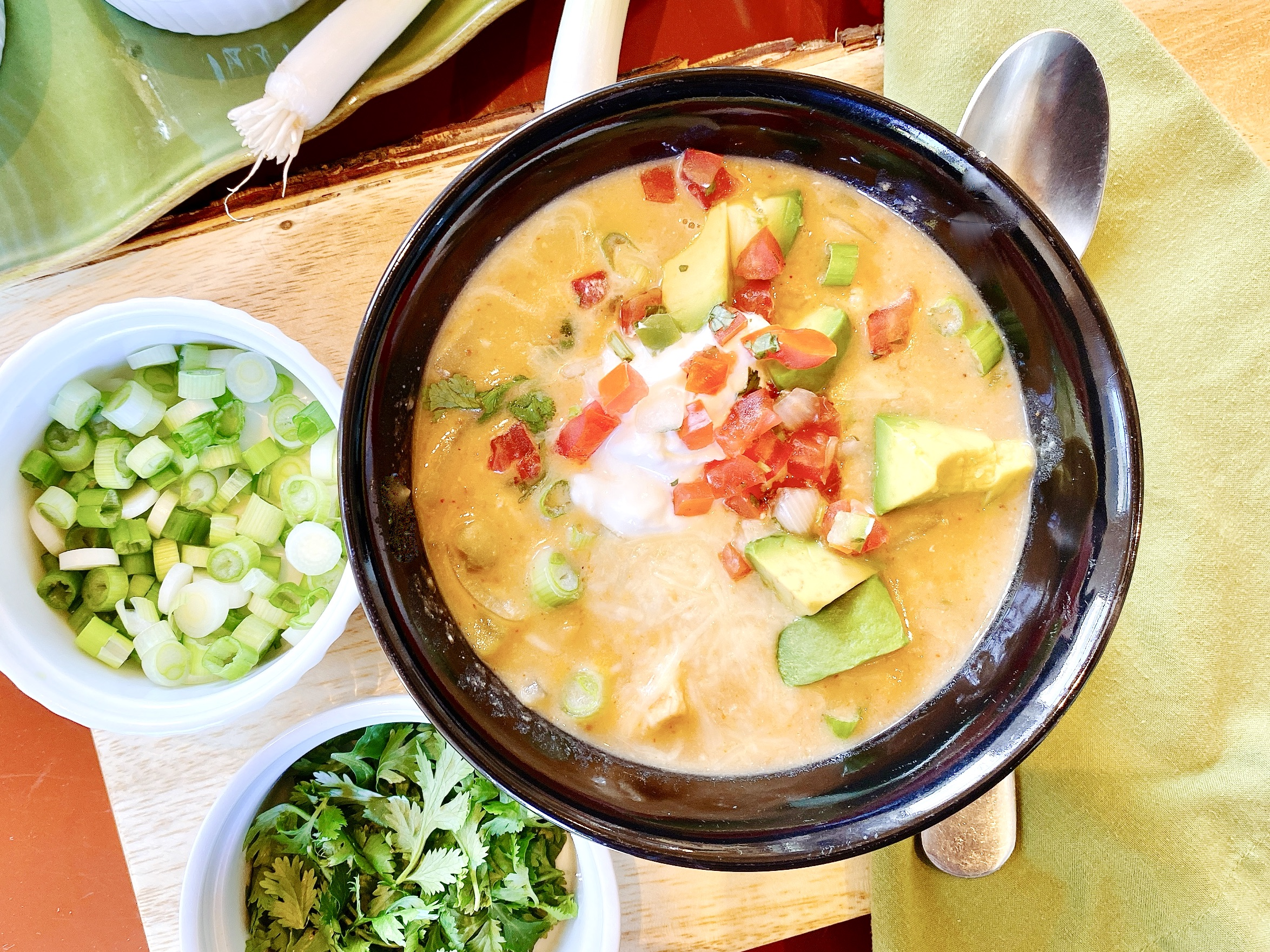 bowl of white chicken chili topped with tomato salsa, sour cream, cheese, green onions and avocado