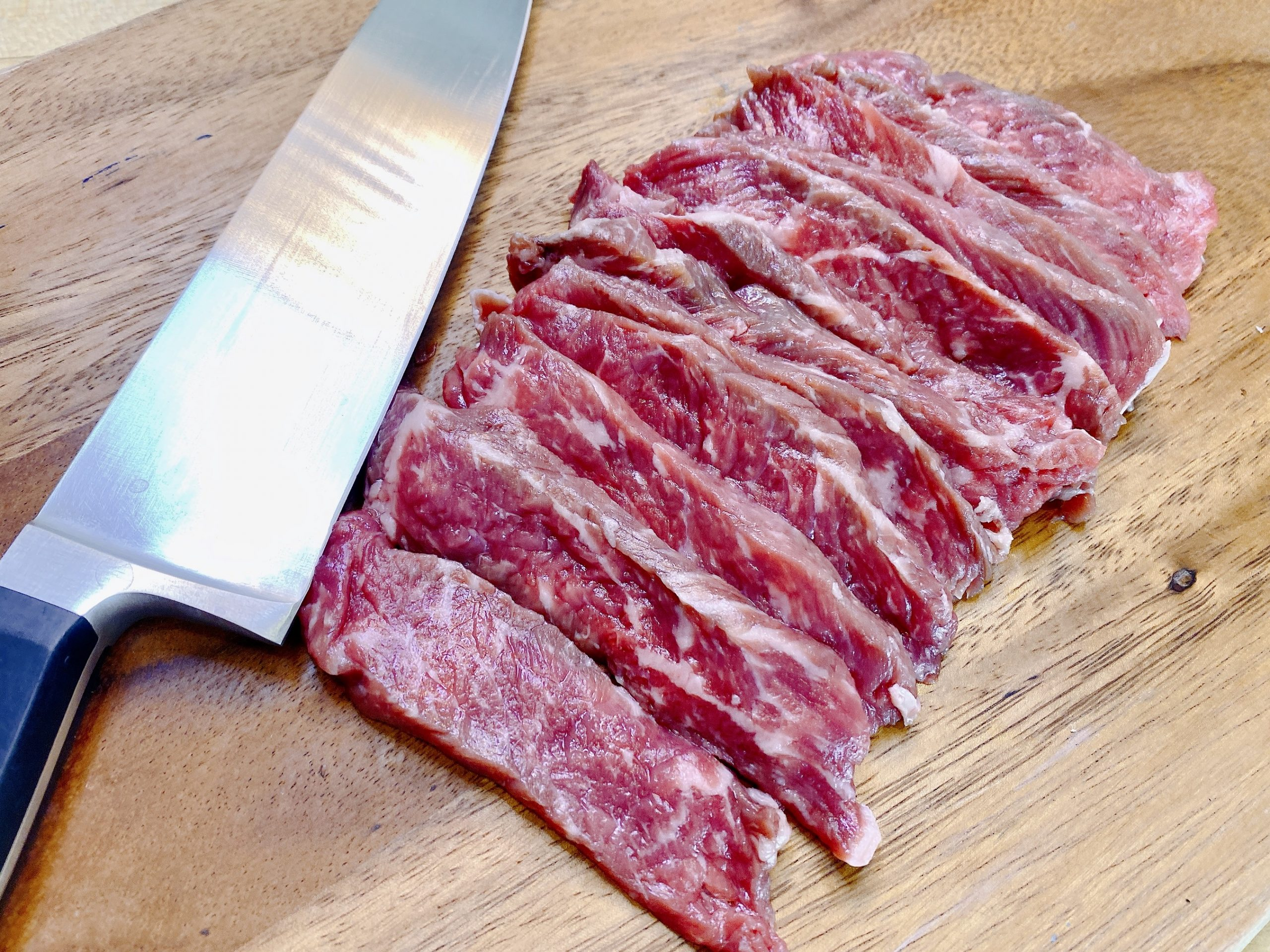 sliced raw steak with knife on cutting board