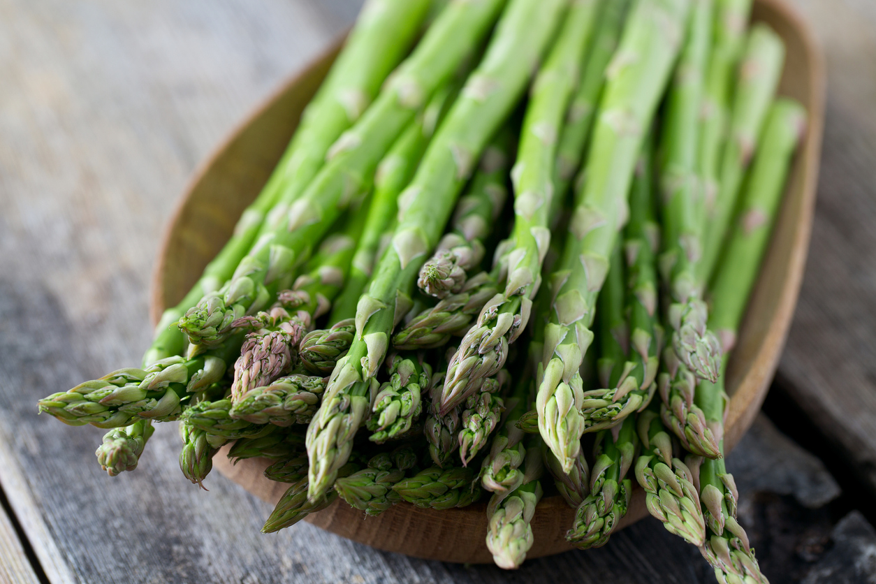 fresh asparagus on wooden surface