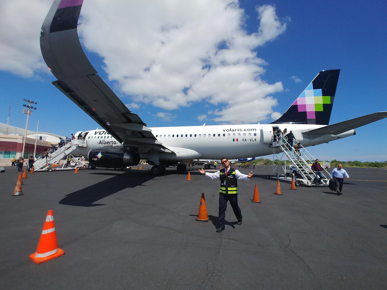 man welcomes guests on tarmac at Loreto Airport as they deplane from Volaris Airlines