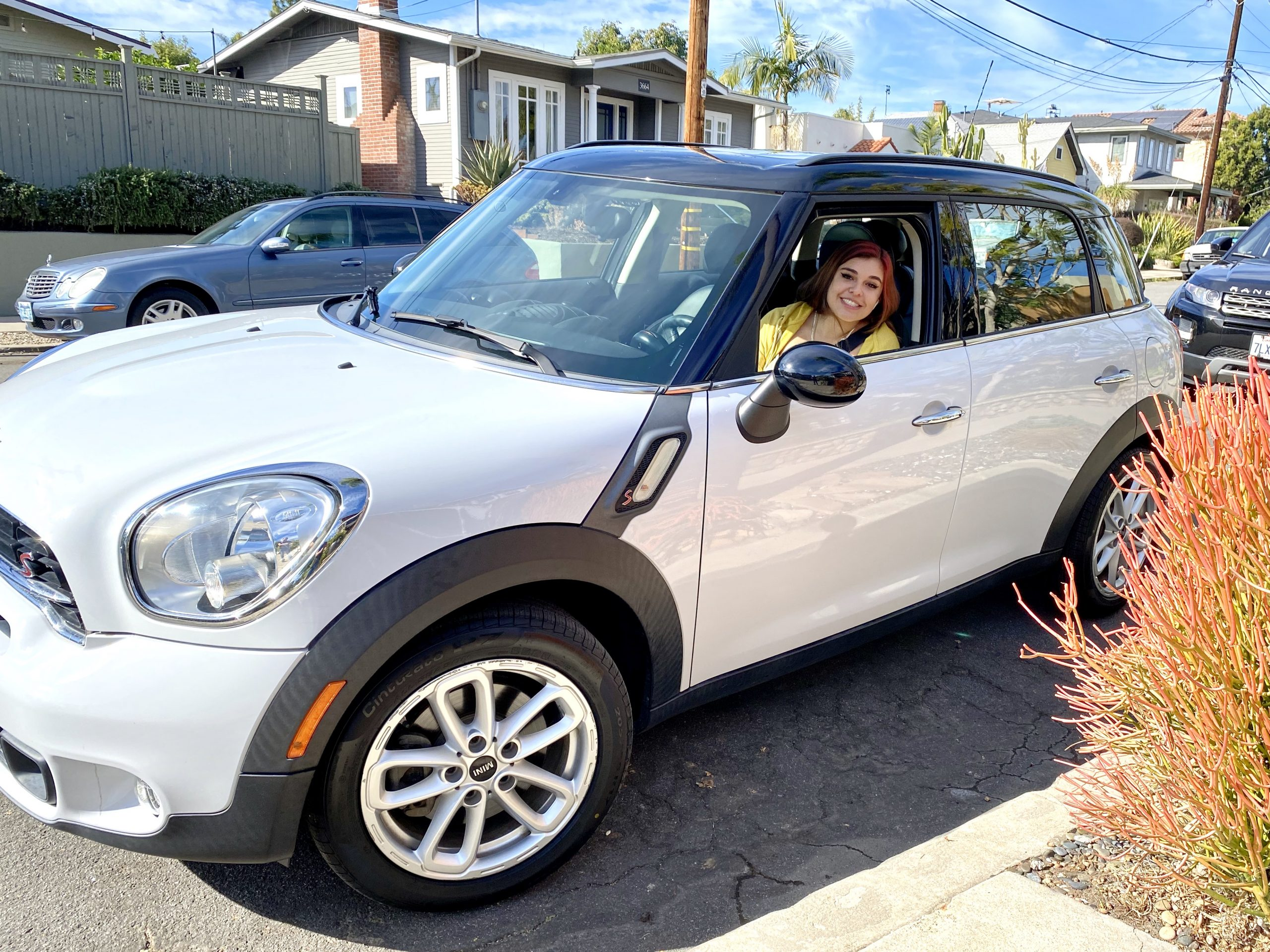 girl smiles from window of Mini Cooper Countryman on street in San Diego, CA