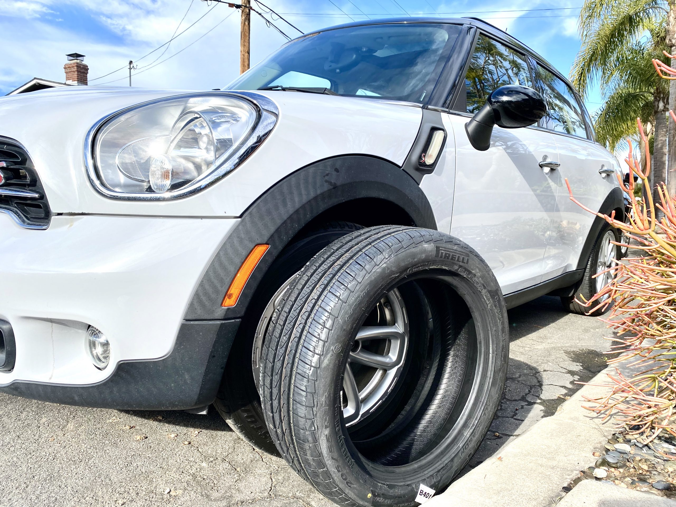 new Pirelli tire in front of old mounted tire on white Mini Cooper Countryman