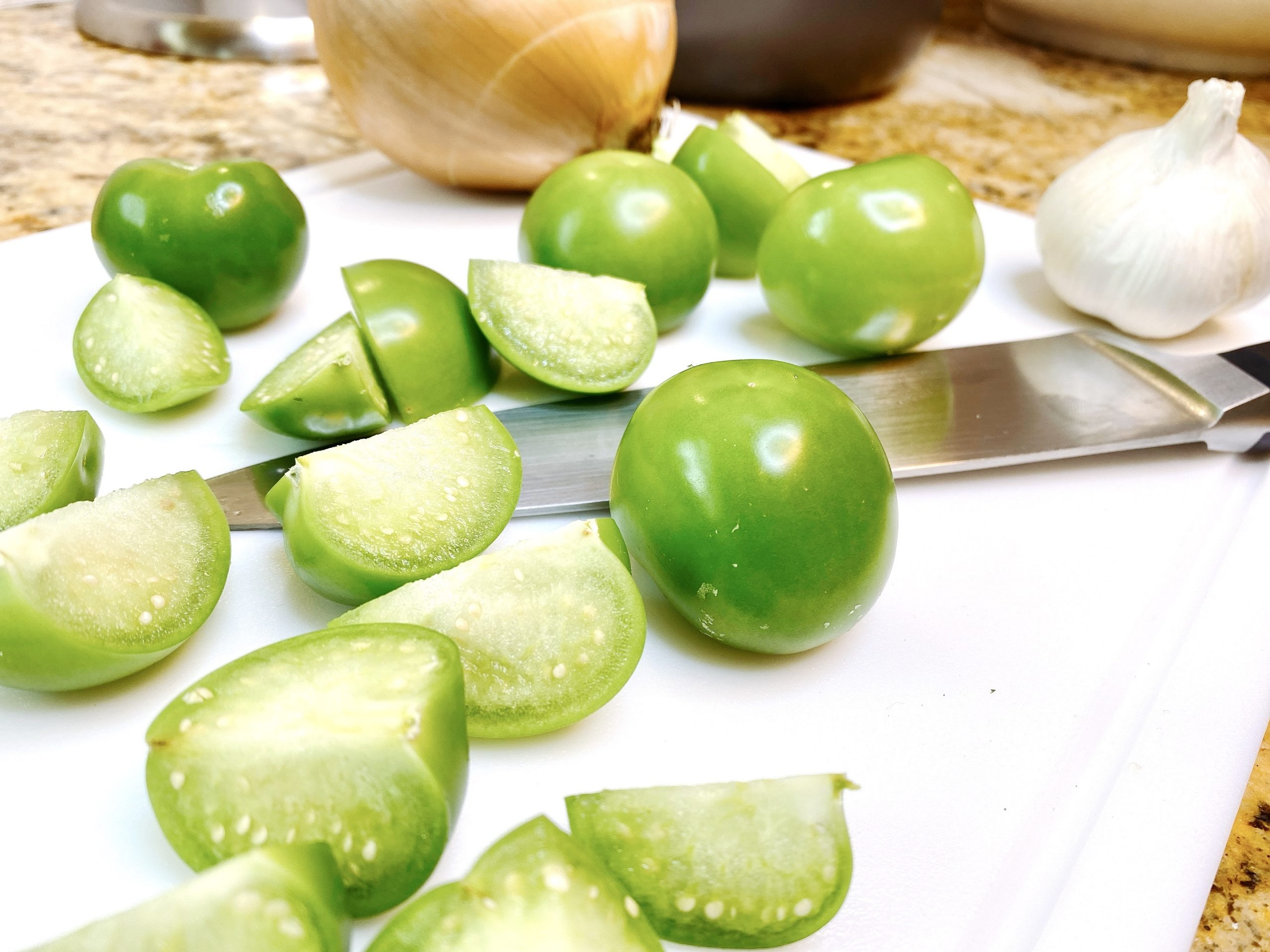 Fresh green tomatillos chopped on cutting board with knife
