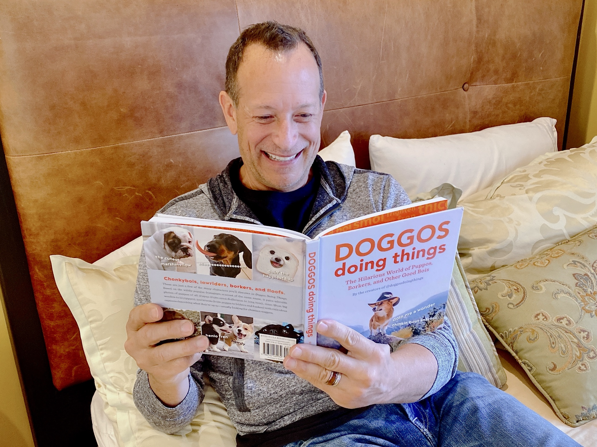 smiling man reading Doggos Doing Things book