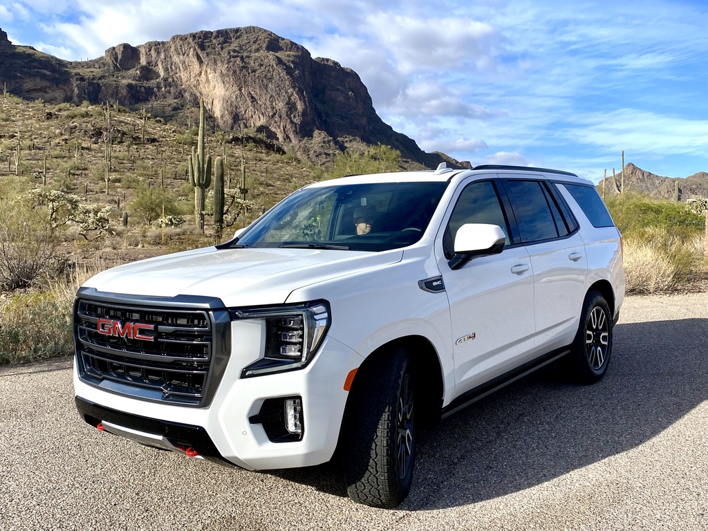White 2021 GMC Yukon AT4 with Arizona desert cactus and mountain backdrop while on the road between Phoenix and Tucson, Arizona
