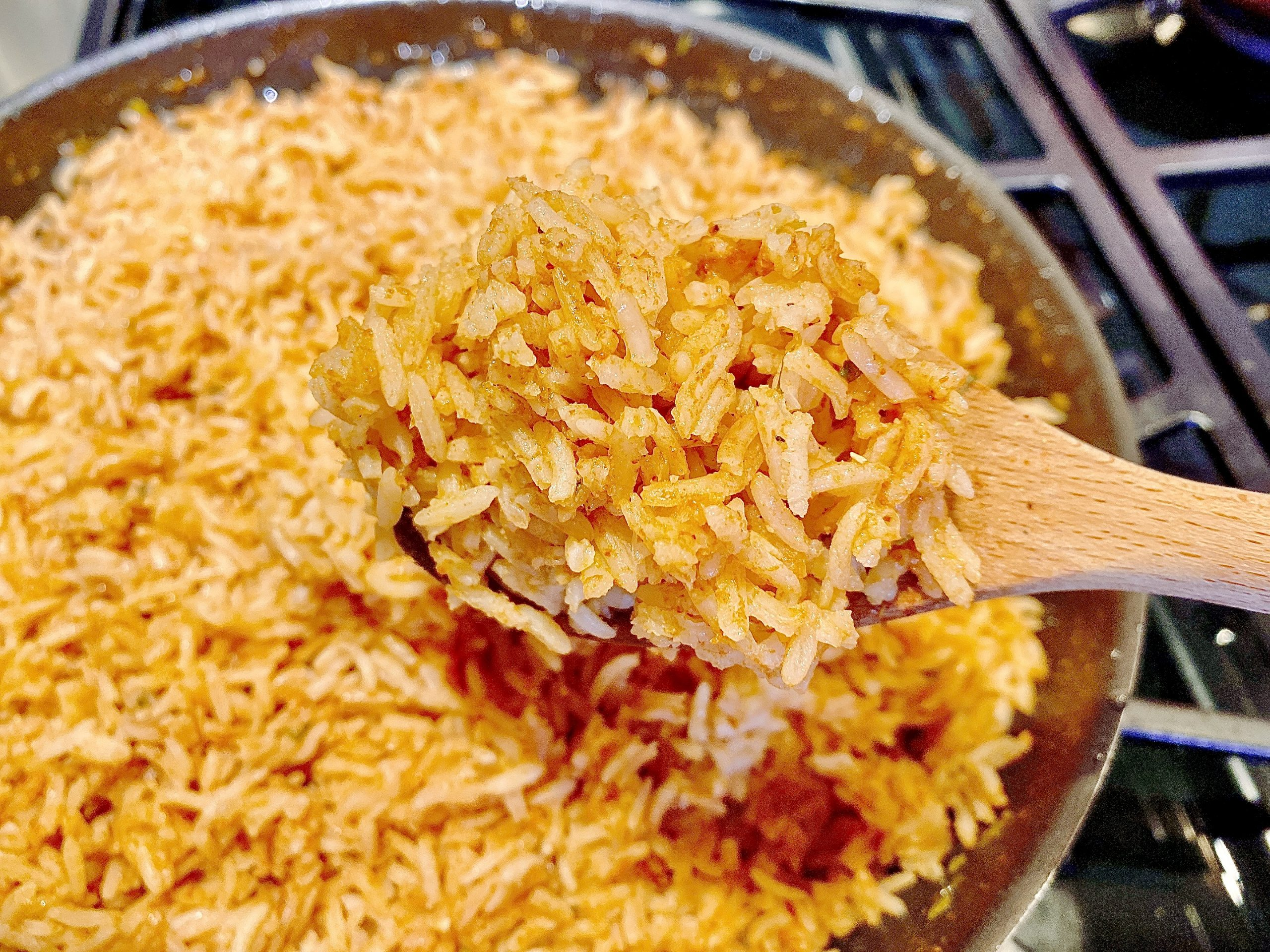 Mexican rice recipe in a pan with large wooden spoon