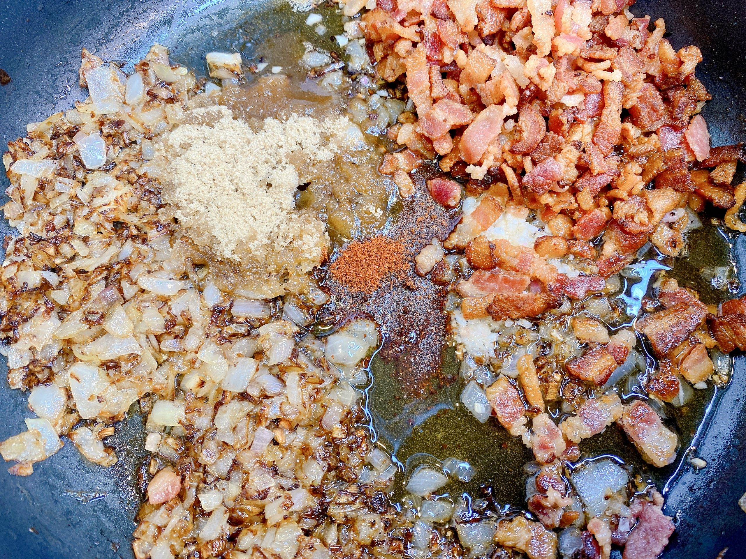 Recipe for Bacon Jam ingredients in frying pan including fried bacon pieces, caramelized onions, brown sugar, maple syrup, cider vinegar and chili powder.