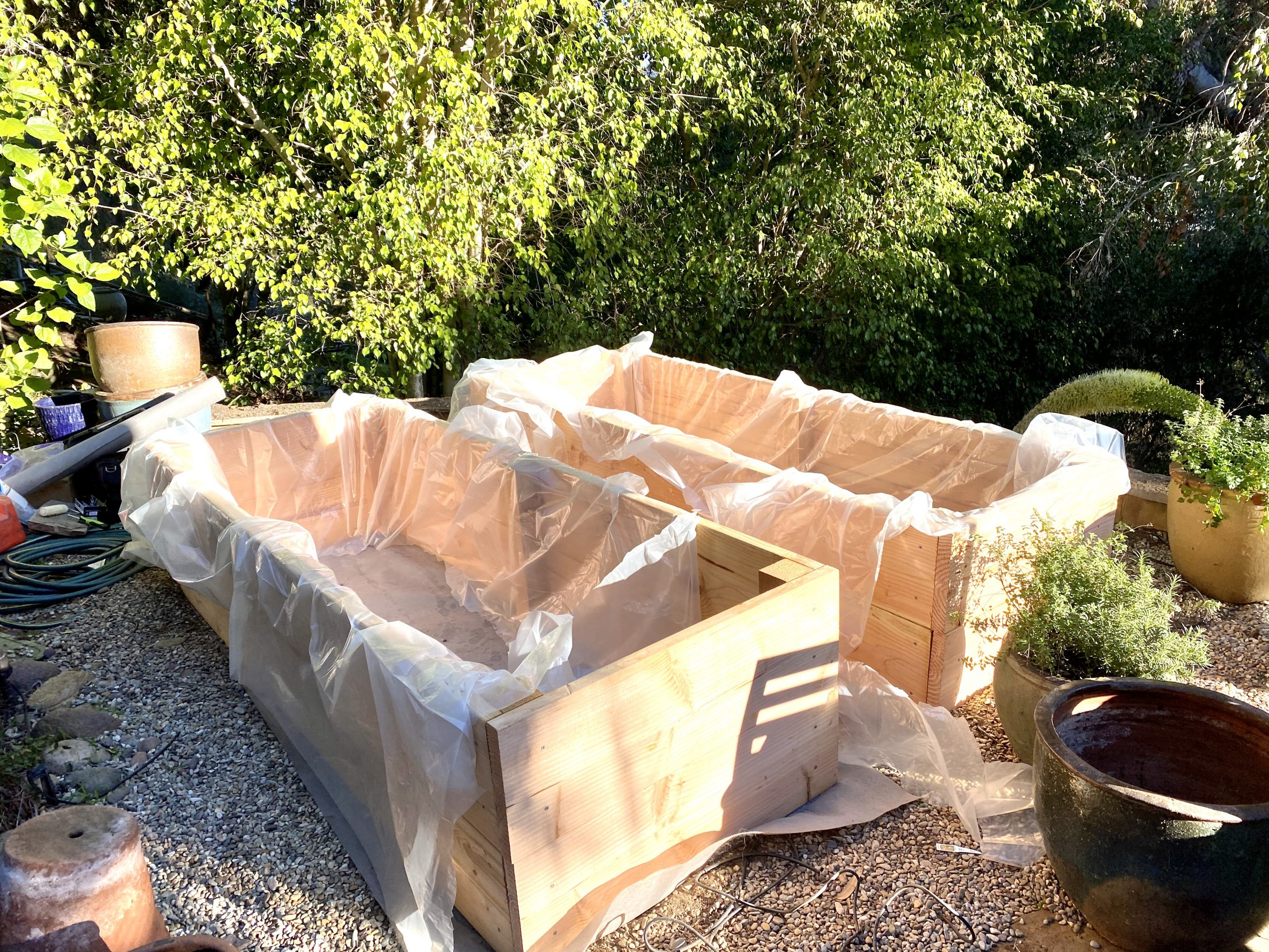 vegetable garden beds under construction with plastic sheeting liners