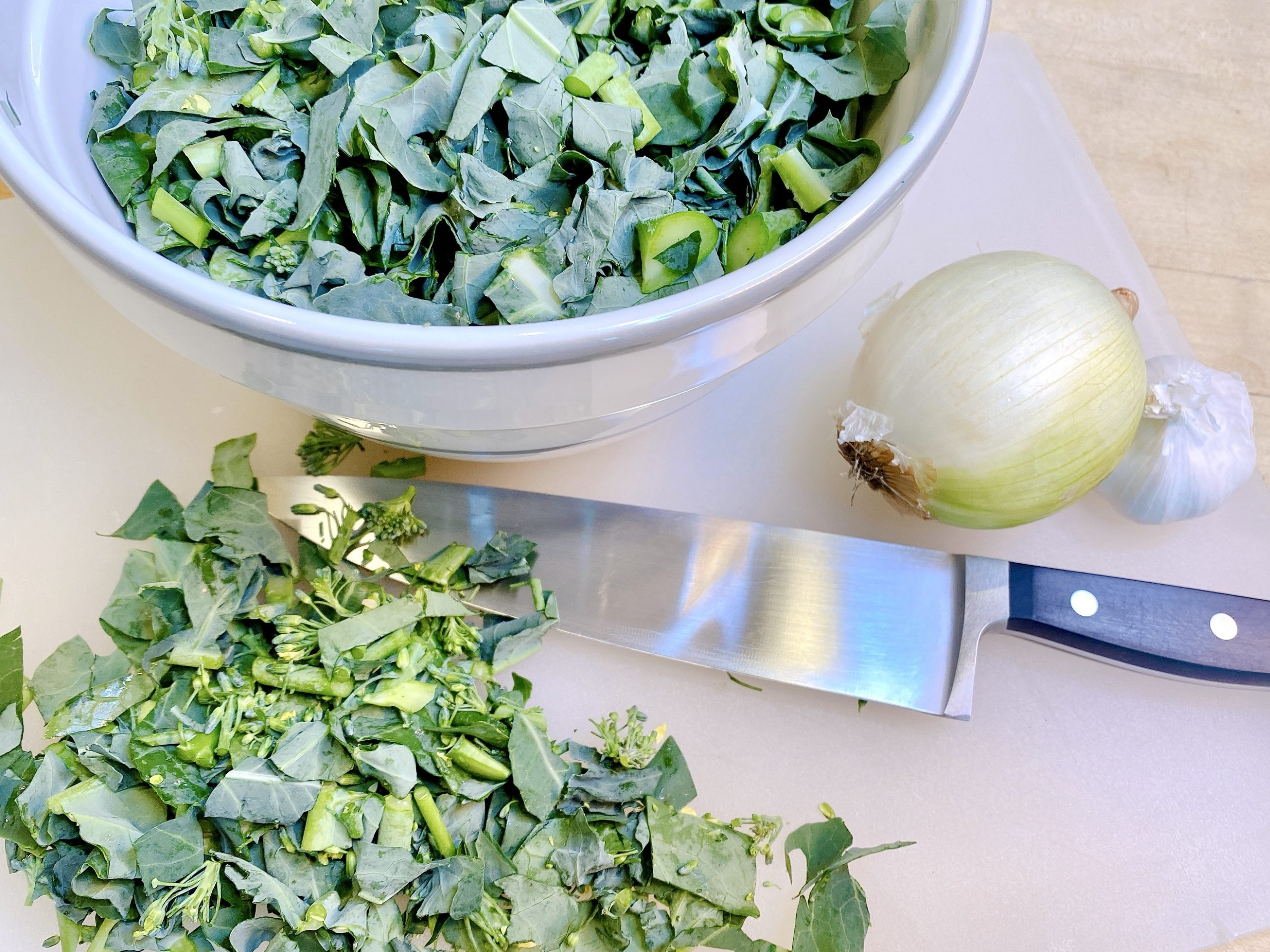 chopped broccoli rabe in bowl and on cutting board with knife