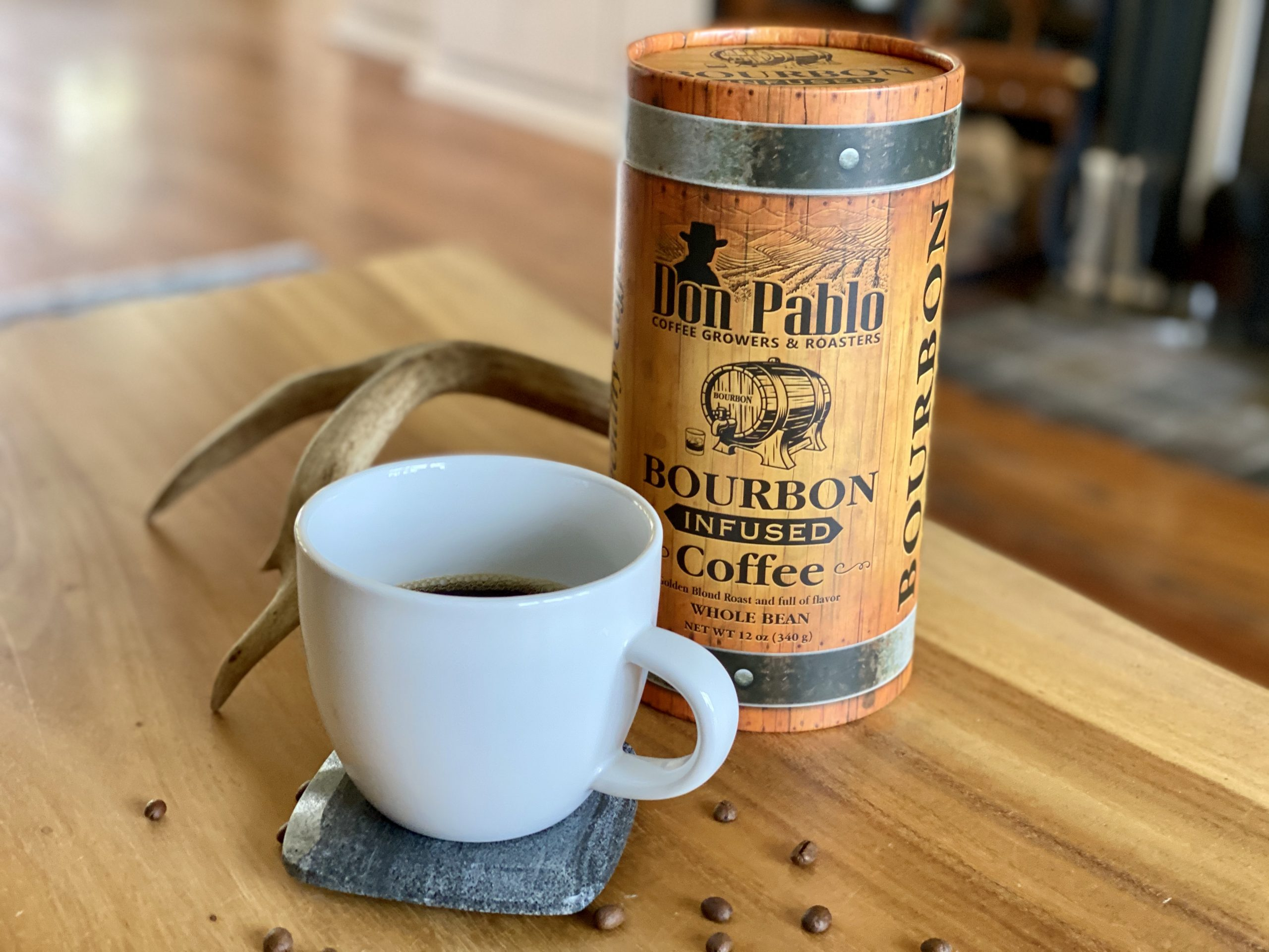 Don Pablo Bourbon Infused Coffee beans with cup of brewed coffee