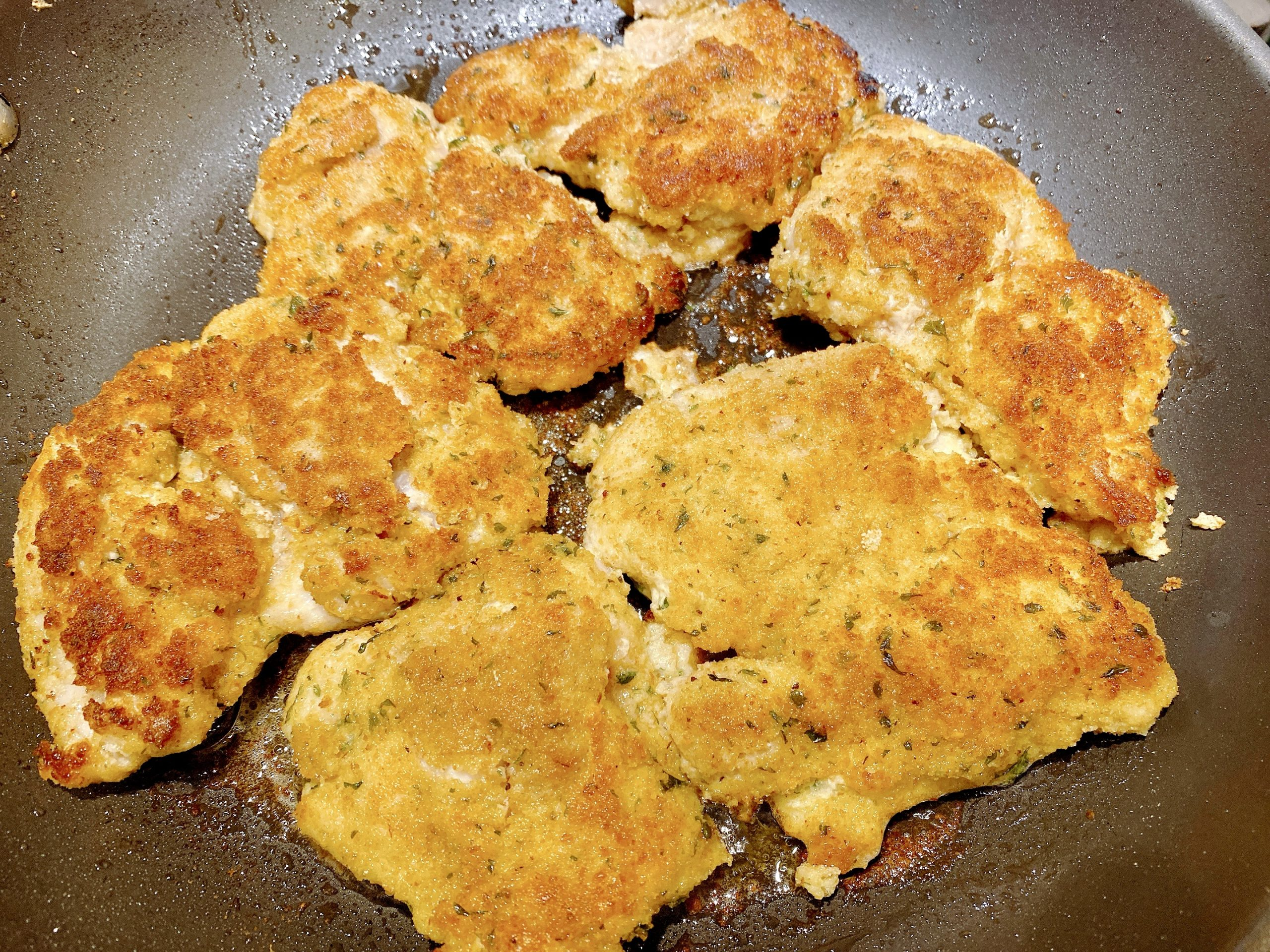 Breaded chicken breasts fried in pan of olive oil